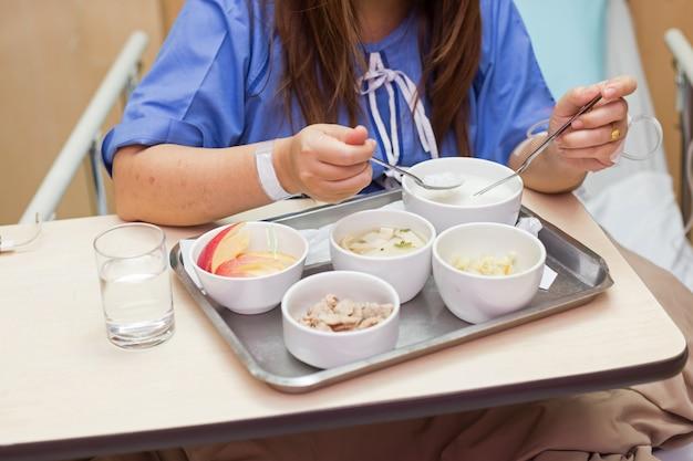 Frauenpatient sitzen auf bett im krankenhauszimmer und essen lebensmittel