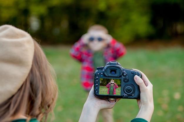 Frauenphotograph, der das kind fotografiert, um draußen im park zu verbringen