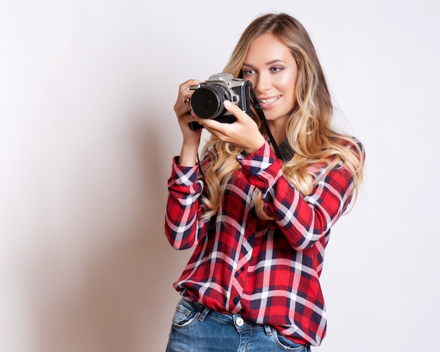 Frauenphotograph mit kamera gegen grauen hintergrund
