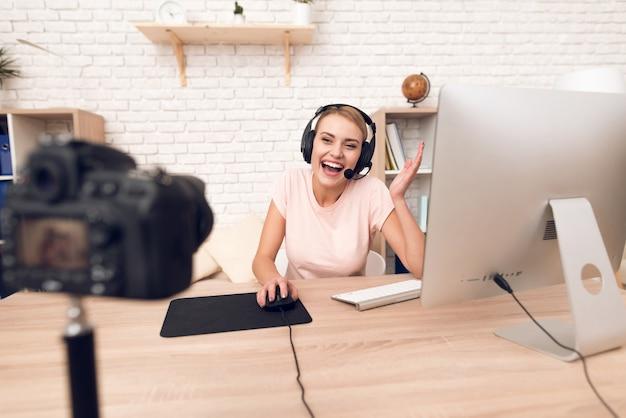 Frauenpodcaster, der an der kamera für radiopodcast aufwirft.