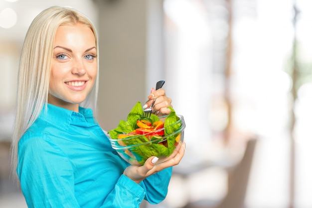 Frauenporträt, das grünen salat mit tomaten isst