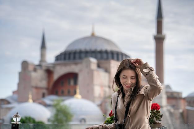 Frauenporträt, das in istanbul nahe berühmter islamischer marksteinmoschee hagia sophia sich entspannt.