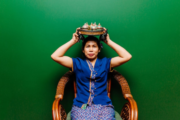 Frauenporträt der thailändischen spa-masseurin mit antiken benjarong-keramikschalen auf korbtablett mit elefanten auf ihrem kopf und traditioneller spa-kleidung, die im rattanstuhl sitzt