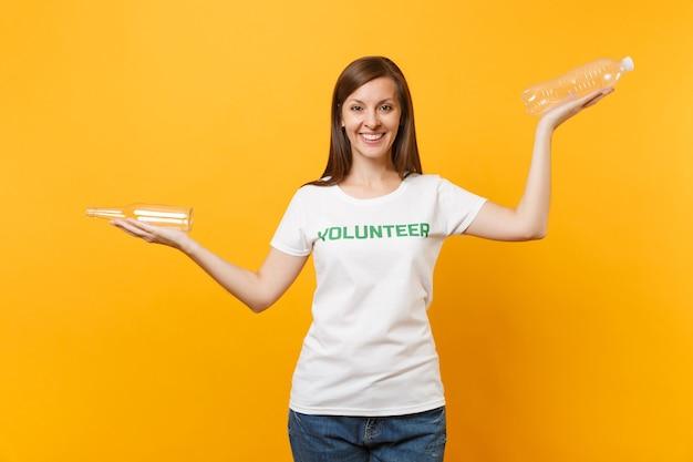 Frauenporträt im weißen t-shirt mit schriftlicher aufschrift grüner titelfreiwilliger halten plastik- und glasflaschen einzeln auf gelbem hintergrund. freiwillige kostenlose hilfe, müllsortierarbeitskonzept.
