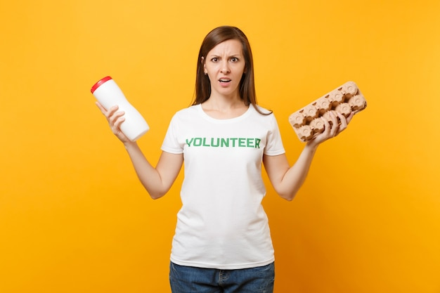 Frauenporträt im weißen t-shirt mit schriftlicher inschrift grüner titel freiwilliger halten plastikflasche, karton isoliert auf gelbem hintergrund. freiwillige kostenlose hilfe, müllsortierkonzept.