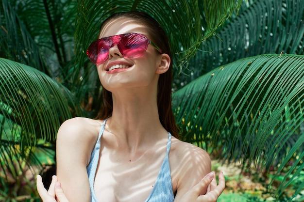 Frauenporträt in den gläsern auf einem hintergrund der grünen blätter der palmen, schönes gesicht