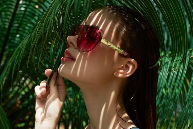 Frauenporträt in den gläsern auf einer oberfläche der grünen blätter der palmen, schönes gesicht