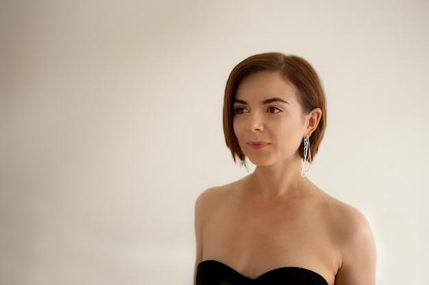 Frauenporträt mit großen silbernen ohrringen, nahaufnahme auf ein make-up. schöner junger gesichtsporträtstil.