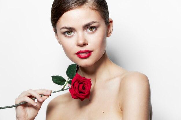 Frauenporträt rote lippen rose blume saubere haut modell lange haare hellen hintergrund