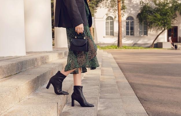 Frauenpose in schwarzen stiefeletten mit minitasche auf der treppe, streetstyle-outfit