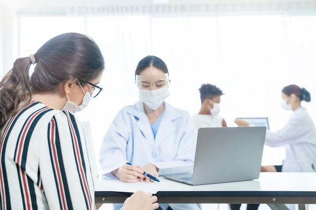 Frauenregistrierung, um covid-impfstoff im krankenhaus zu erhalten, frau mit schutzmaske gegen covid19