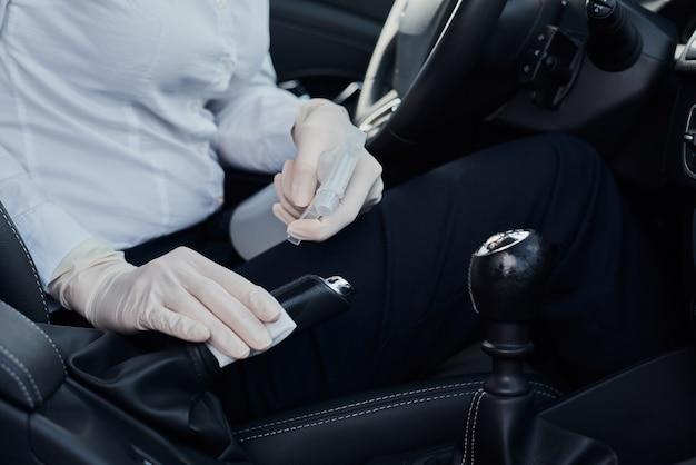 Frauenreinigungsauto mit desinfektionsspray zum schutz vor coronavirus