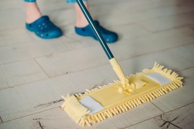 Frauenreinigungsboden mit gelbem mopp zu hause. mikrofasermopp isoliert auf weißem holzbodenhintergrund, nahaufnahme, drinnen