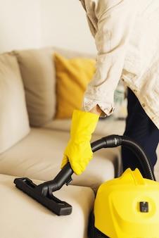 Frauenreinigungssofa mit gelbem staubsauger. sauberes konzept