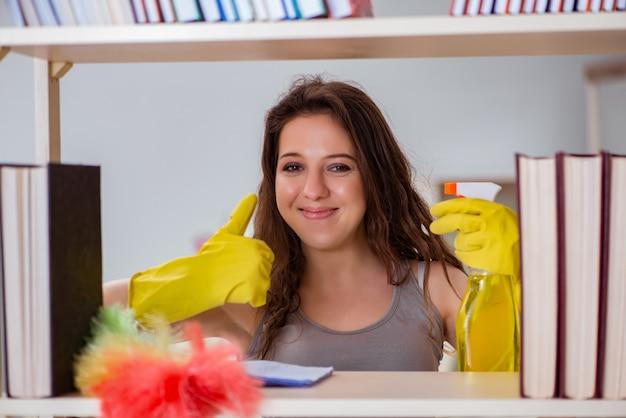 Frauenreinigungsstaub vom bücherregal