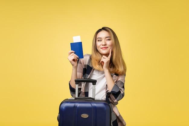 Frauenreise junger schöner asiatischer frauenreisender, der pass hält