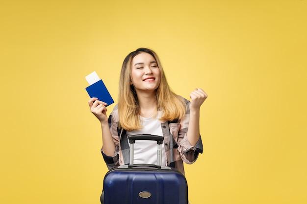 Frauenreise. junger schöner asiatischer reisender, der pass, koffer und flugticket hält