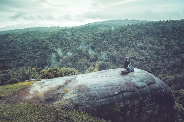 Frauenreisen sitzen auf einer klippe auf einem reichen waldberg. asien tropisch