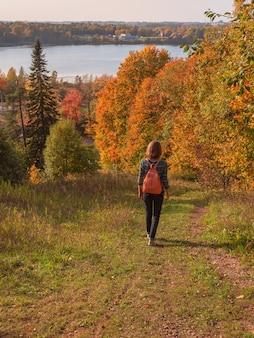 Frauenreisende, die mit rucksack am herbsthügel wandern. reisen lifestyle konzept abenteuerurlaub im freien. vertikale ansicht.