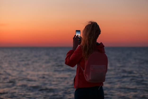 Frauenreisende, die smartphone verwenden und den bunten seesonnenuntergang fotografieren.