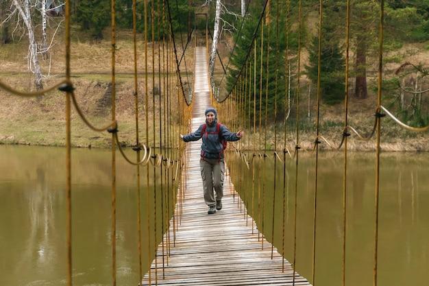 Frauenreisende geht entlang der hängebrücke über den quellfluss
