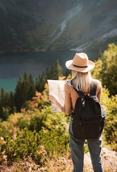 Frauenreisende mit hut und blick auf erstaunliche berge und see, fernweh-reisekonzept. see morskoy eye in der polnischen tatra.
