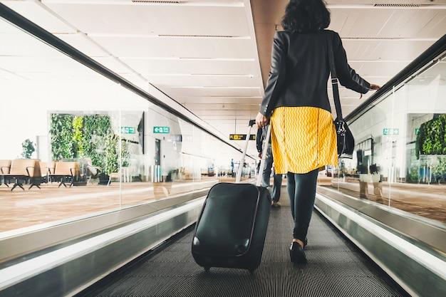 Frauenreisende mit reisekoffer oder -gepäck, die auf dem gehweg des flughafenterminals für urlaubsreisen ins ausland gehen. konzept der reise um die welt, tourismus. brünette im gelben rock geht auf rolltreppe.