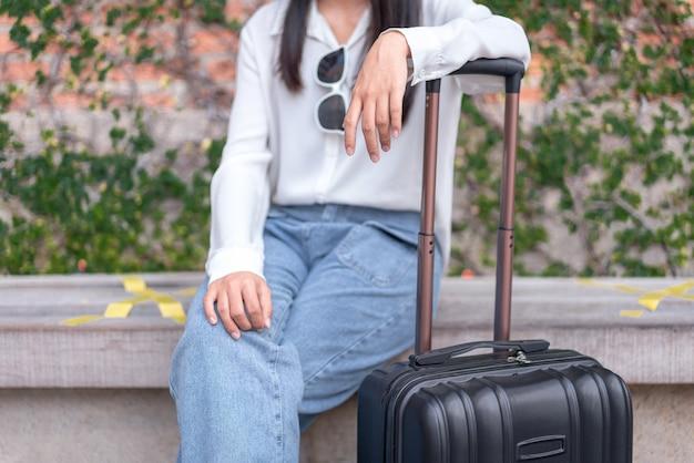 Frauenreisende sitzend und ziehen schwarzes koffergepäck, während sie zum einsteigen in den flughafen gehen, reisekonzept.