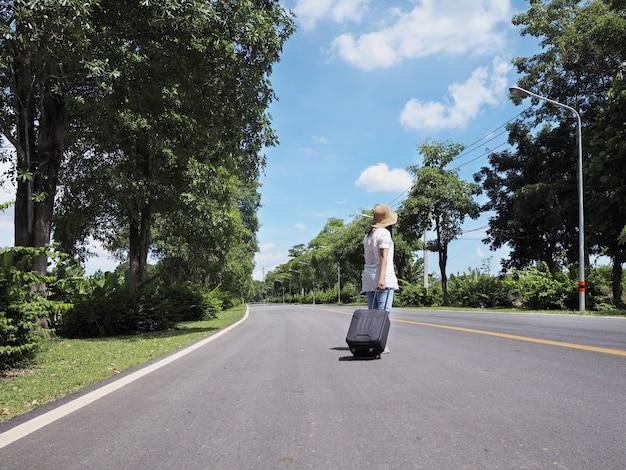 Frauenreisender, der alleine mit gepäck entlang der straße geht