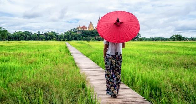 Frauenreisender, der asiatische reisfeldlandschaft wandert.
