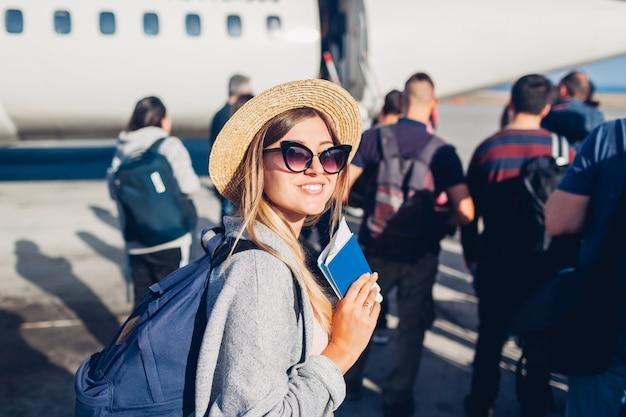 Frauenreisender, der auf dem flugzeug hält pass einsteigt. glücklicher passagier mit dem rucksack, der in der linie bereit zum flug steht