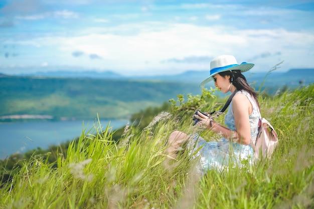 Frauenreisender, der auf dem gras sitzt und fotoansicht der verdammung und des berges macht