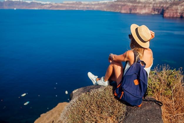 Frauenreisender, der auf dem rand des felsens kessel von akrotiri, santorini-insel, griechenland betrachtend sitzt. tourismus, reisen