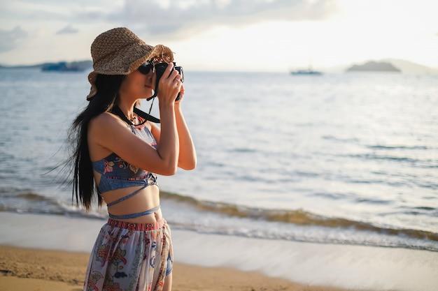 Frauenreisender, der auf dem strand steht und foto für ansicht des meeres macht