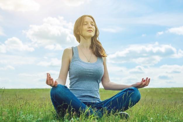 Frauenreisender, der auf der wiese mit grünem gras unter blauem himmel mit wolken in der lotusposition sitzt