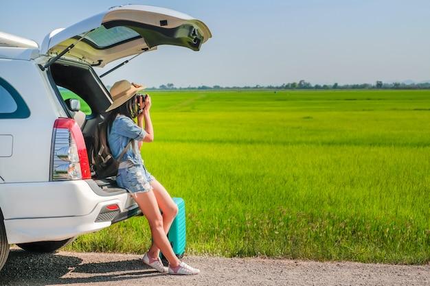 Frauenreisender, der auf fließheck des autos sitzt und foto macht
