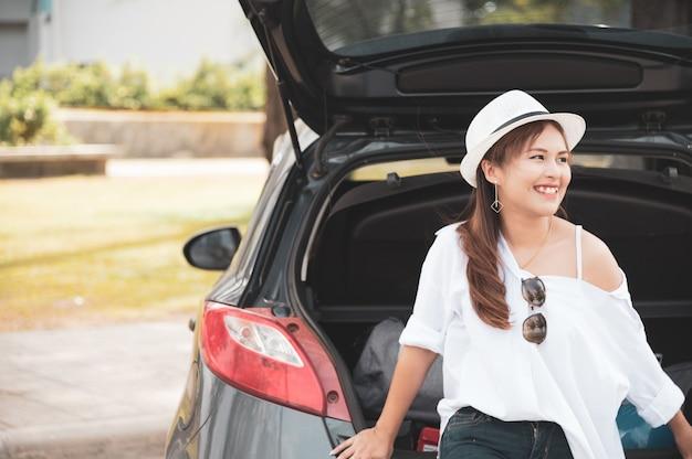 Frauenreisender, der auf hatchbackauto sitzt