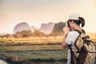 Frauenreisender, der bei Gebirgssonnenuntergang fotografiert