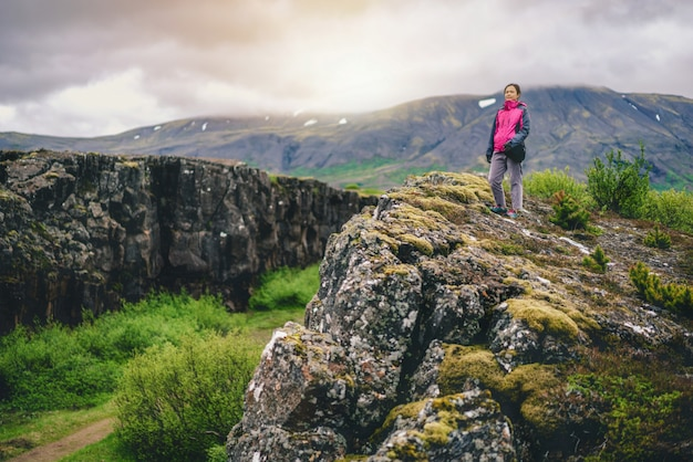 Frauenreisender, der durch islandlandschaft wandert.