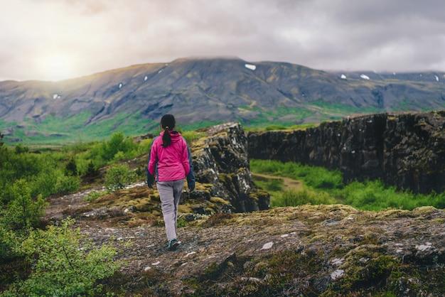 Frauenreisender, der durch islandlandschaft wandert