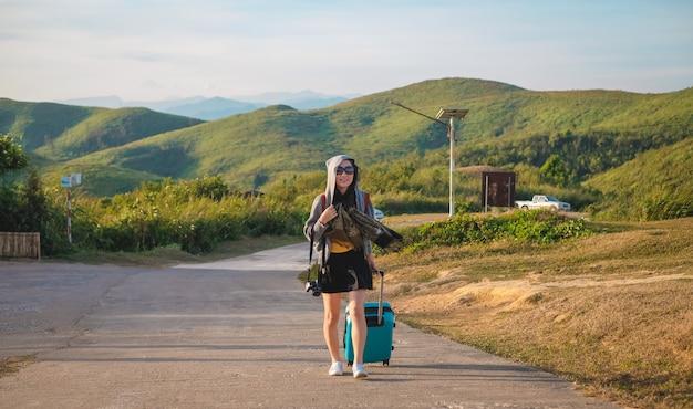 Frauenreisender, der ein gepäck trägt und nach ansicht der natur sucht
