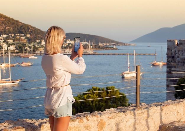 Frauenreisender, der foto von bodrum castle bei sonnenuntergangslicht macht. reisekonzept, türkischer urlaub.