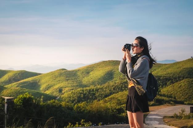 Frauenreisender, der fotoansicht der natur am feiertag macht.