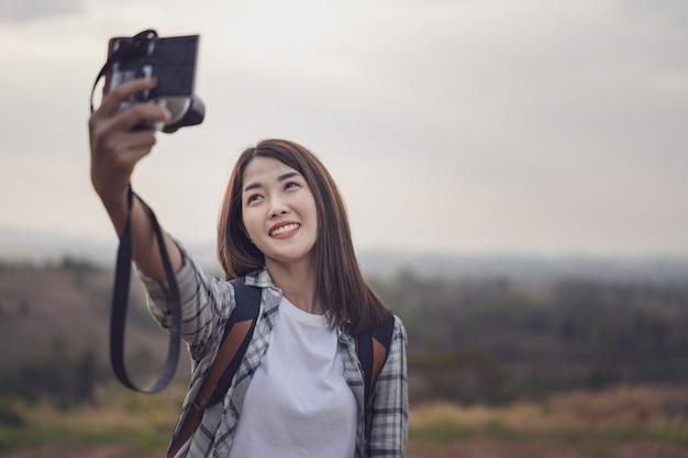 Frauenreisender, der kamera zur herstellung von selfie im gebirgswald verwendet