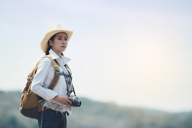 Frauenreisender, der mit rucksack an der gebirgslandschaft wandert
