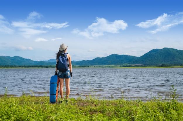 Frauenreisender, der nahe dem see im berg steht