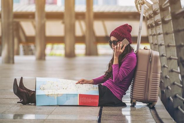Frauenreisender, der reisekarte im flughafengehweg mit tasche oder gepäck betrachtet.