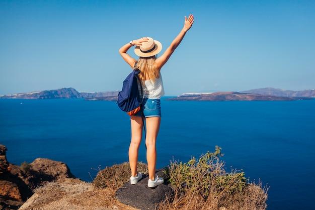 Frauenreisender hob die arme an, die glücklich sind, kessel von akrotiri, santorini-insel, griechenland betrachtend. tourismus, reisen