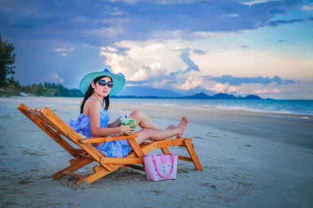 Frauenreisender im sexy schwimmenanzug, der auf dem stuhl sitzt und für ansicht von meer genießt