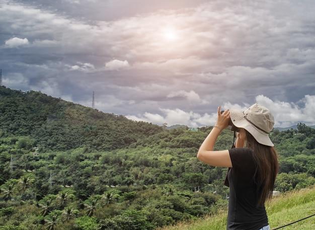 Frauenreisender machen fotoansicht des grünen berges mit ihrer kamera am feiertag